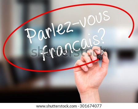Man Hand writing Parlez-vous français? (Do You Speak French? In French) with black marker on visual screen. Isolated on office. Business, technology, internet concept. Stock Photo