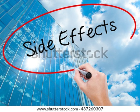 Man Hand writing Side Effects with black marker on visual screen. Business, technology, internet concept. Modern business skyscrapers background. Stock Photo