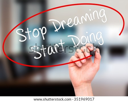Man Hand writing Stop Dreaming Start Doing  with black marker on visual screen. Isolated on background. Business, technology, internet concept. Stock Photo