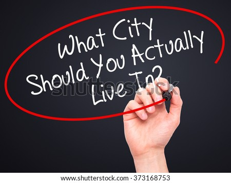 Man Hand writing What City Should You Actually Live In? with black marker on visual screen. Isolated on background. Business, technology, internet concept. Stock Photo