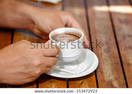 Man hands holding cup of coffee at cafe outdoors summer. Male drink cappuccino in restaurant closeup. Coffee time and breakfast. Man with mug of hot chocolate enjoying life in cafe.