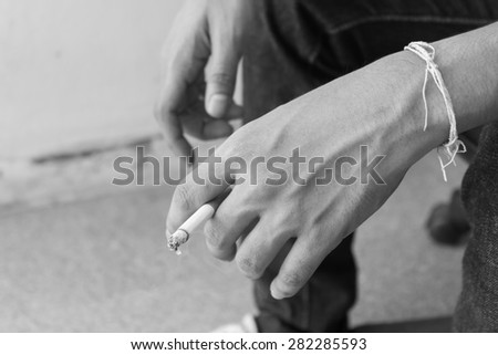 Man hold burning cigarette in his hand