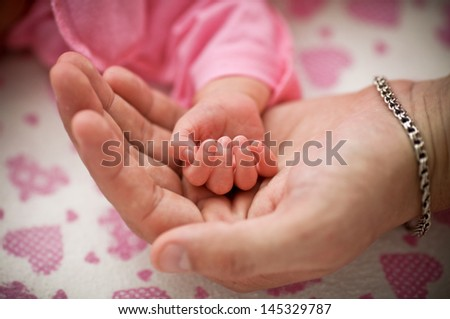 man holding a baby hand, extreme closeup