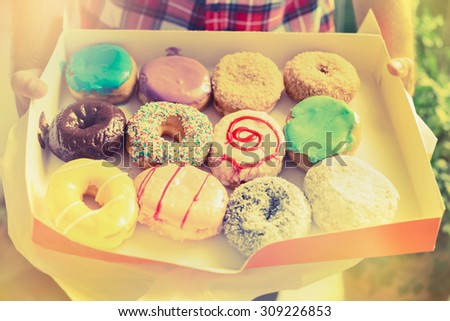 man holding a box with colorful glazed doughnuts  on background of a sunny nature,close up, retro toned