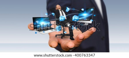 Man holding a businessman in his hand connected to modern devices