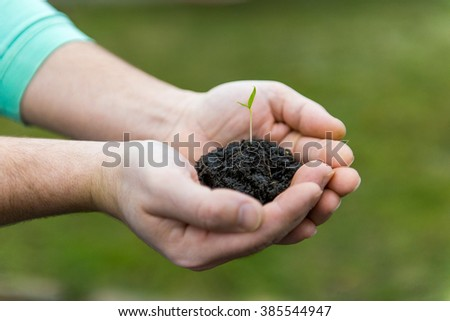 man holding a handful of earth with a young green shoots.