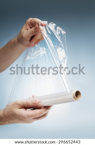 Man holding a roll of plastic film, typically used for sealing food items.