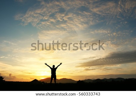 Man holding arms up in praise to God against sunrise at morning  background.