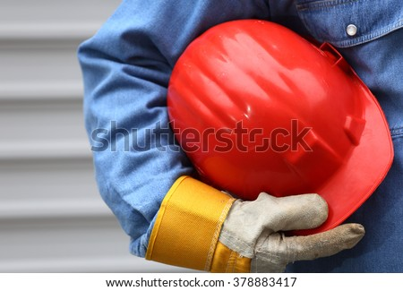 Man holding red helmet close up, shallow dof