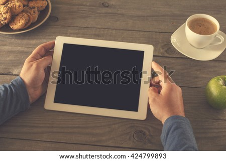 man holding tablet computer with blank screen for your text sitting behind a rustic wooden table at home