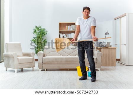 Cleaning The House man husband cleaning house helping wife stock photo 582226093