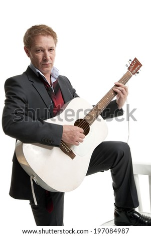 man in a black suit playing acoustic guitar isolated on white background