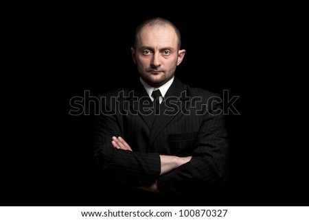 Man in black suite whit arms crossed, in black background