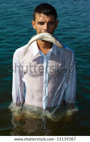 man in classic white shirt walking in water bearing fish in his mouth like a predator
