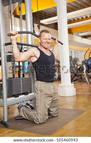man in his forties training latissimus in gym