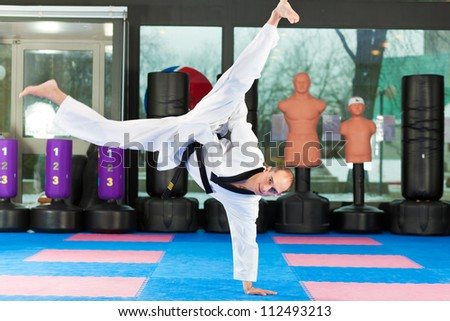Man in martial art training in a gym, he is wearing a black belt