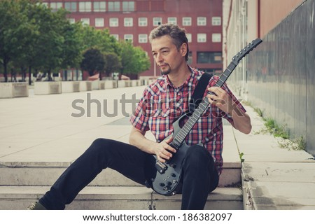 Man in short sleeve shirt playing electric guitar in the street