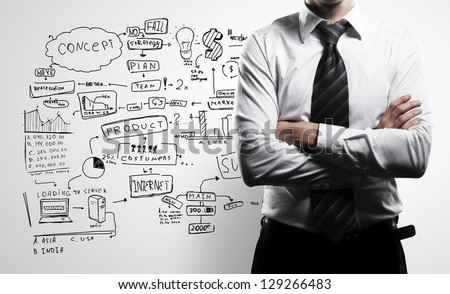 man in suit and business plan on wall