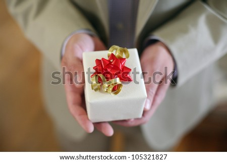 Man in Suit Holding a Wrapped Gift