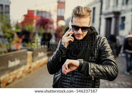 Man in the city talking on the phone and looking at smartwatch