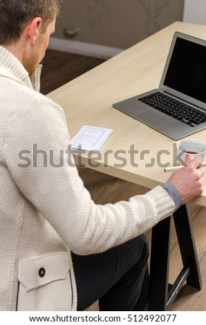 Man in white jacket holding a cup of coffee and holding a pencil