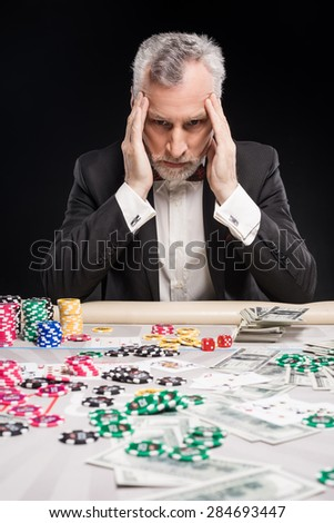 Man in years sitting at poker table and considering poker strategy with his hands on temples. The chips and money are on table