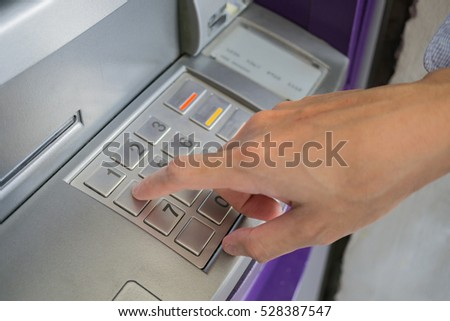 Man is entering number on atm machine to withdraw money