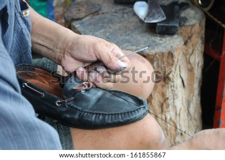 man is repairing leather shoe; an occupation in Thailand