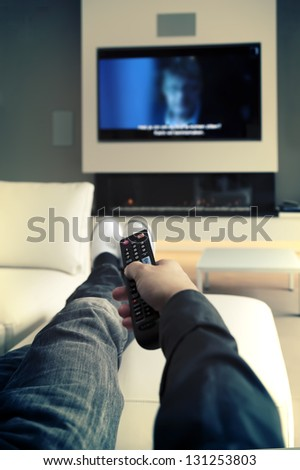 man is watching TV ( focus at distance control)