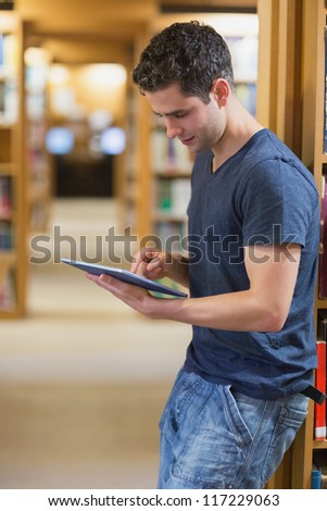 Man leaning against book shelf using tablet pc in college library