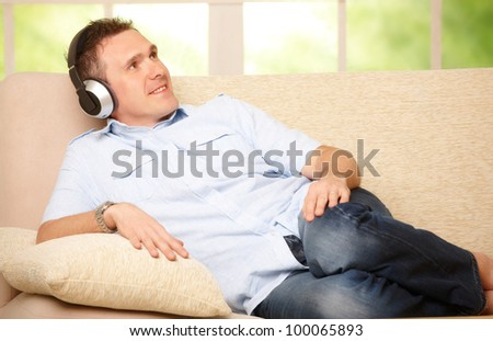 Man listening music with cordless headphones sitting on sofa at home