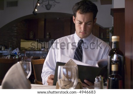 Man looking at a menu in a fancy restaurant