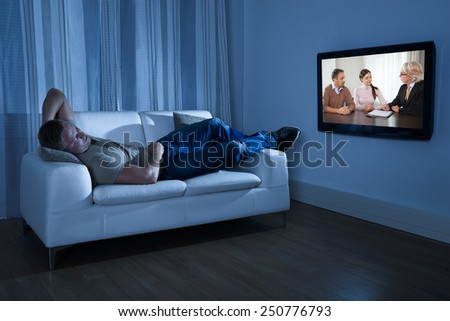 Man Lying On Couch Watching Movie At Home