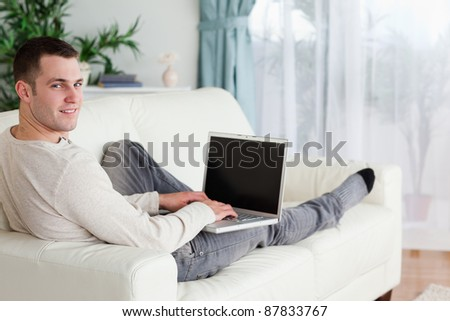 Man lying on his couch with a laptop while looking at the camera