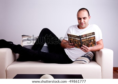 man lying on the sofa reading a book