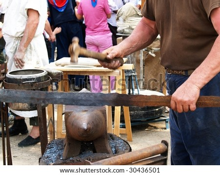 man making an iron blade with anvil and hammer