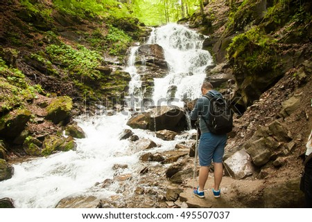 Man making photos of the waterfall in the forest