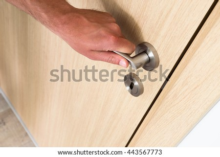 Man opening a light hardwood wooden household door with a close up view of his hand on the handle above a circular keyhole and lock, high angle oblique view with copy space