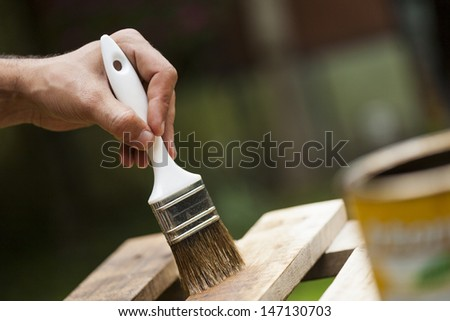 Man painting a wooden deck outdoors - stock photo