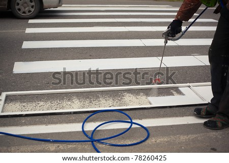man painting crosswalk zebra
