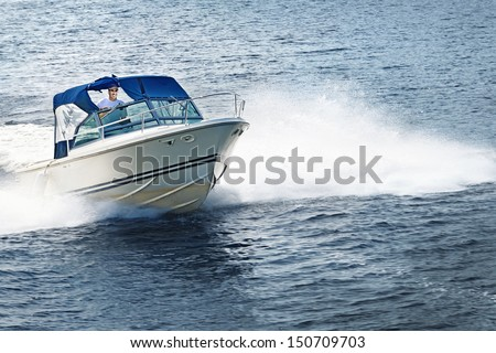 Man piloting motorboat on lake in Georgian Bay, Ontario, Canada.