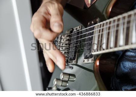 man playing electric guitar close up view, very shallow depth of field image