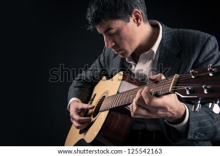 Man playing guitar against black background. Focus on hand.