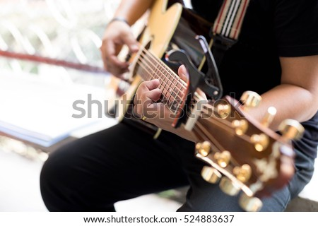 Man Practicing In Playing Acoustic Guitar With A Capo Clip On Neck