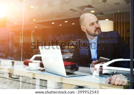 Man professional broker with mobile phone in hands is waiting in cafe clients for conclusion of the transaction at the stock exchange. Male proud financier resting after conference via laptop computer