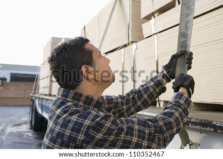 Man pulling trailer belt after loading wooden planks