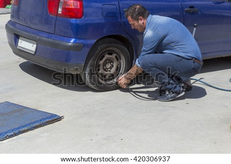 man pumping car tires