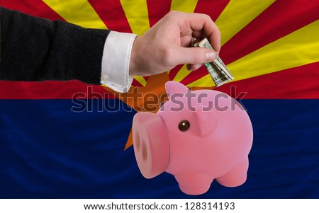 Man putting dollar into piggy rich bank flag of us state of arizona in foreign currency because of inflation