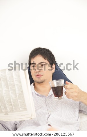 Man reading a newspaper and drinking a coffee