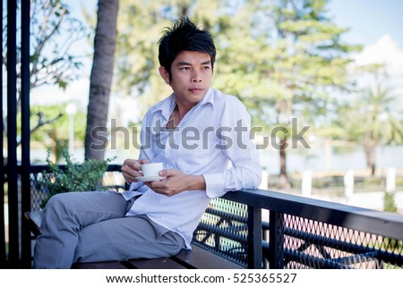Man relaxing at coffee shop on the couch and having a coffee break, he holding a cup